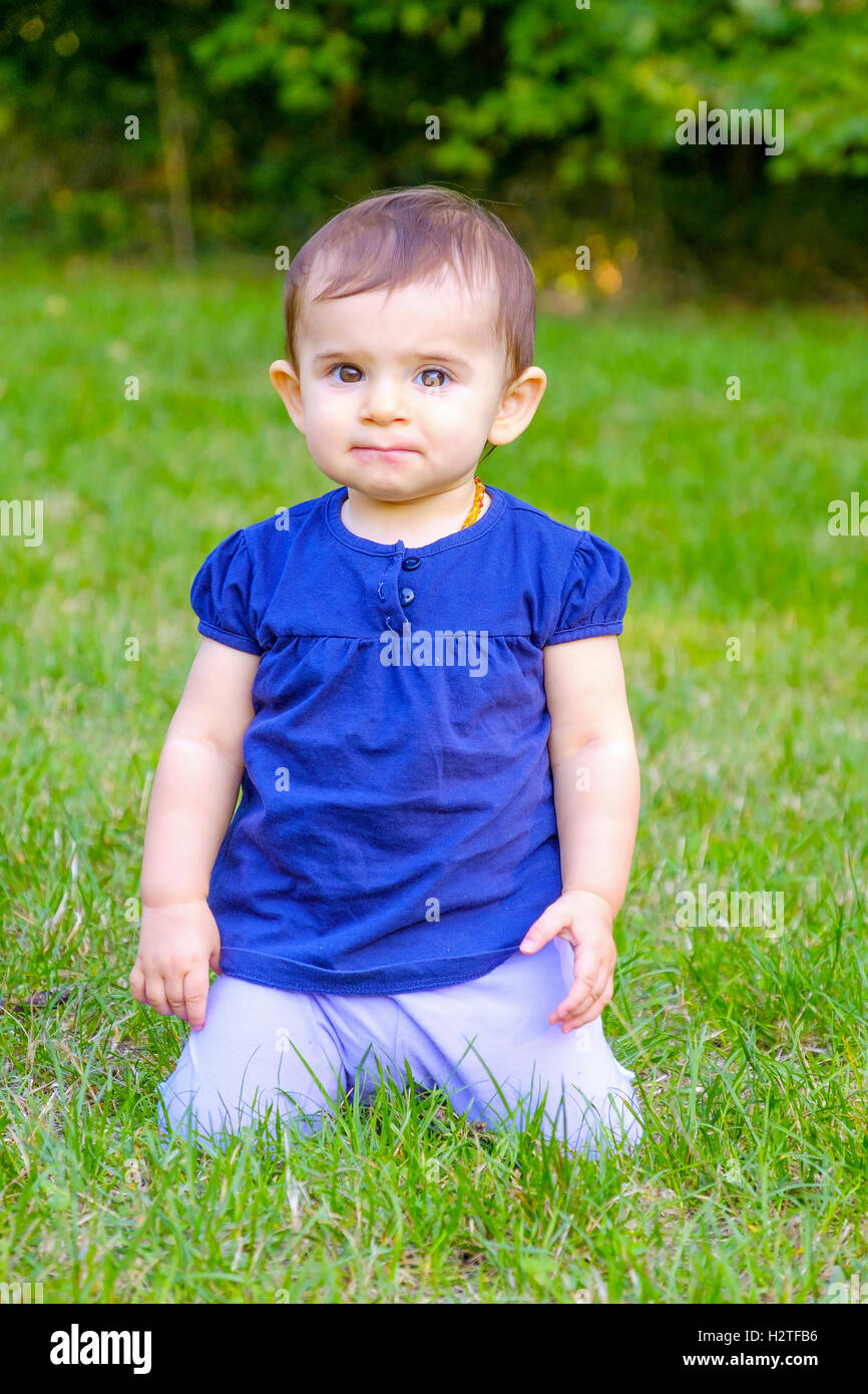 puzzled baby on knees grass - Stock Image