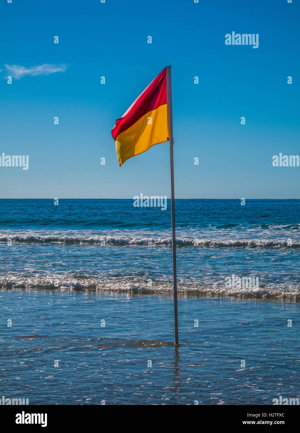 Beachscape with red and yellow flag indicating safe, patrolled beach in Australia - Stock Image