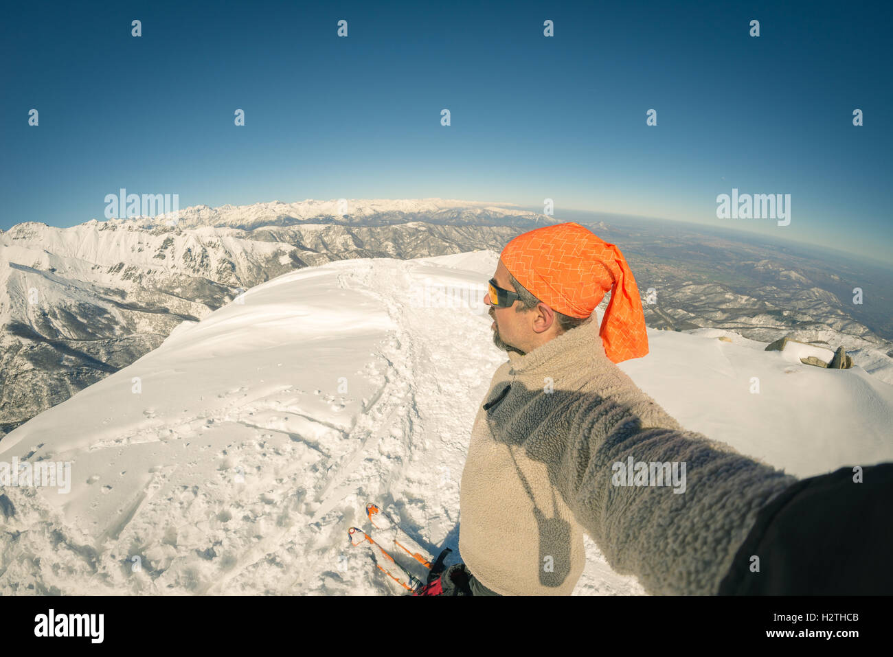 Adult alpin skier with beard, sunglasses and hat, taking selfie on snowy slope in the beautiful italian Alps with - Stock Image