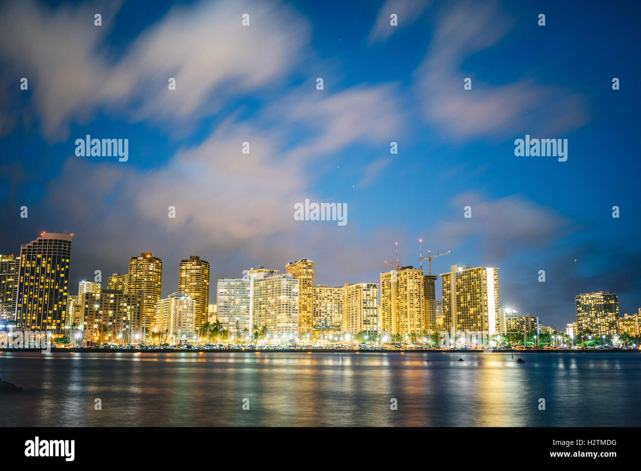 A night view of a section of Honolulu skyline viewed from Magic Island. - Stock Image