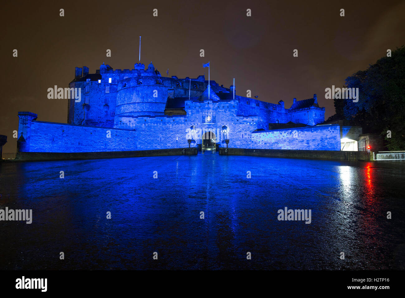 Edinburgh Castle at night bathed in Saltire Blue light - Stock Image