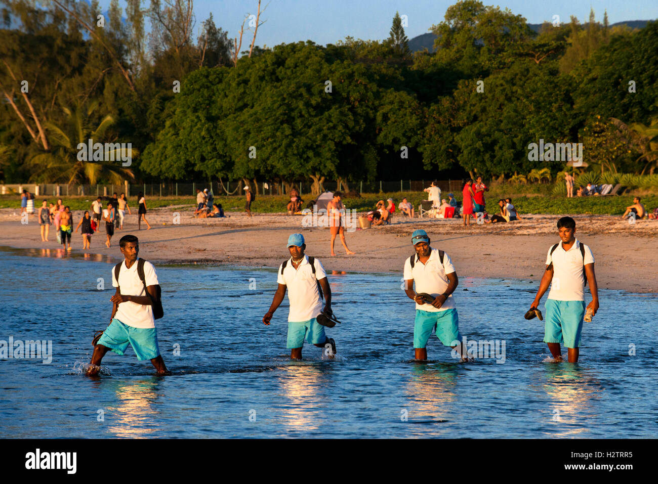 Hotel workers walking in Tamarin beach, Mauritius. Relection in the water. Stock Photo