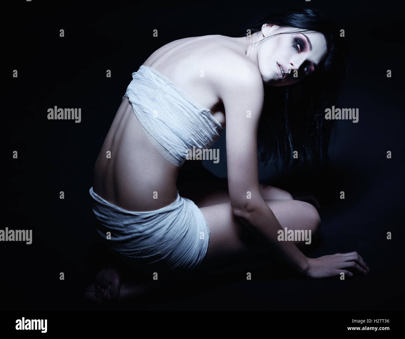 Vampire girl looks to the light - Stock Image