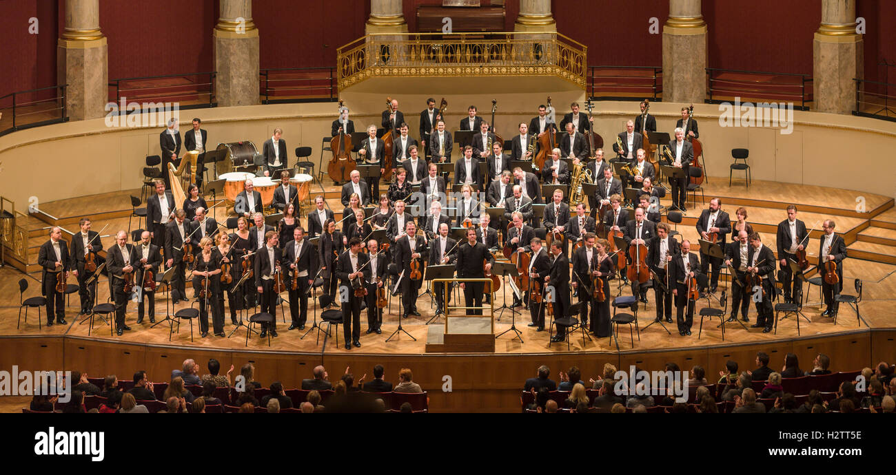 Conductor and Orchestra Applauded. The audience applauds while the players and conductor stand and accept the appreciation. - Stock Image