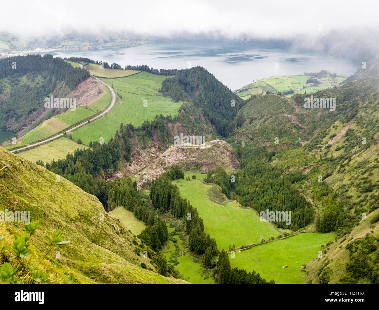 Road between Lagoa Azul and Santiago and Valley below. Mist moves in over a road that runs atop the crater between - Stock Image