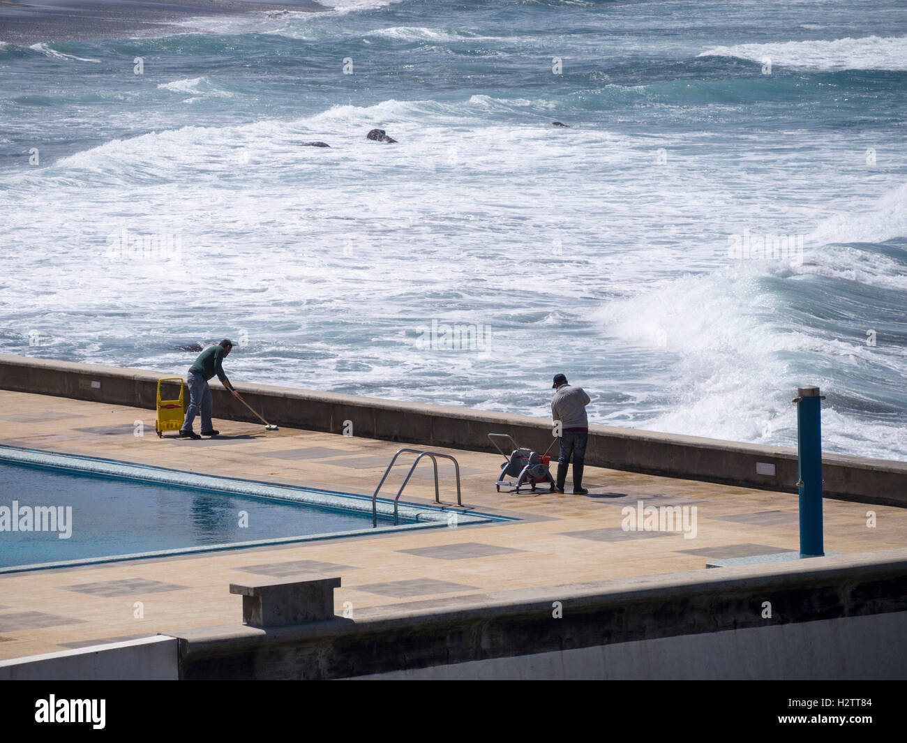 Cleaning Up the Pool. Two workmen scrub the deck of an oceanside swimming pool while behind them large breakers - Stock Image