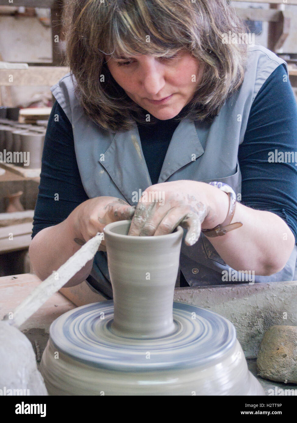 Throwing a pot on a pottery wheel. A craftswoman raises the edges of a tumbler on a spinning wheel. Her hands are - Stock Photo
