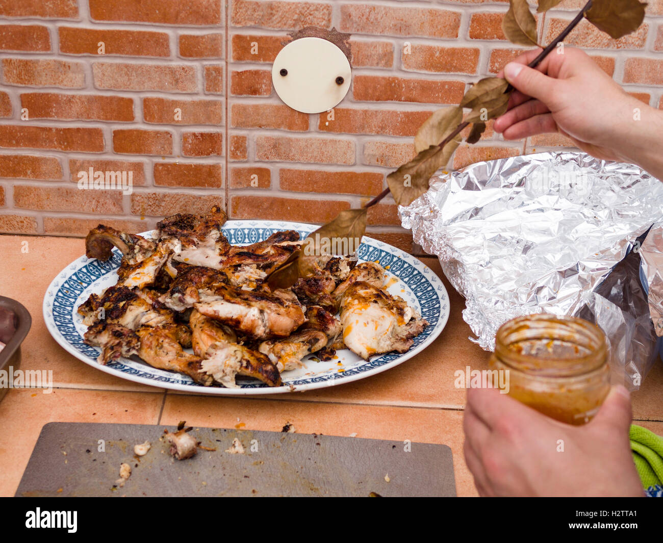 Glazing BBQ Chicken pieces. As a final touch a chef's assistant coats bits of BBQ chicken with a glaze using a leafy Stock Photo