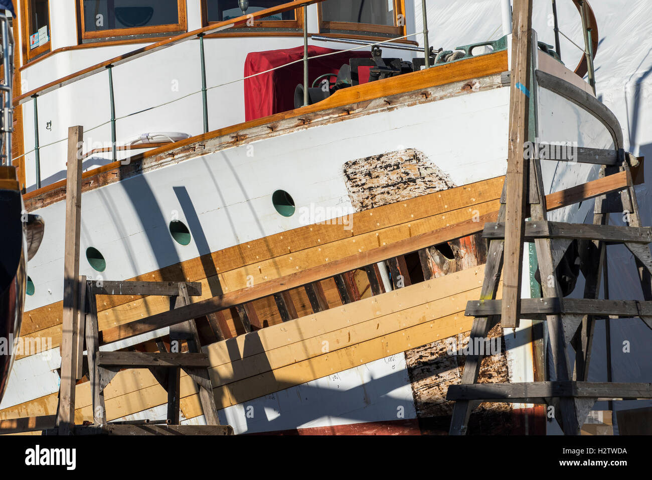 Wooden boat repair at dry dock by shipwright in Port Townsend boat yard. Stock Photo