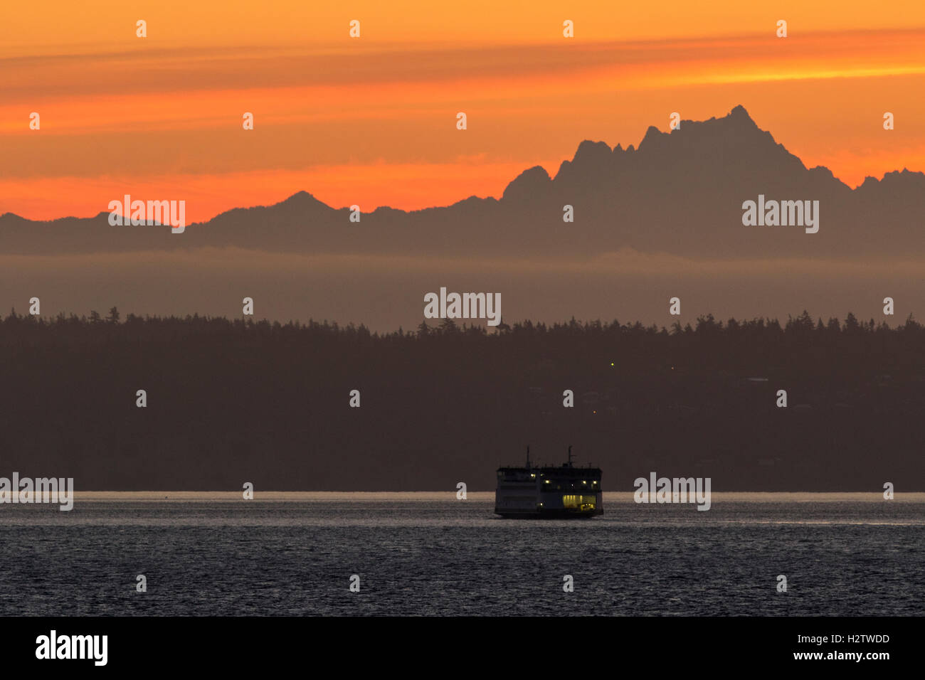 Puget Sound ferry at sunrise with Cascade mountains in background. Washington State ferries. - Stock Image