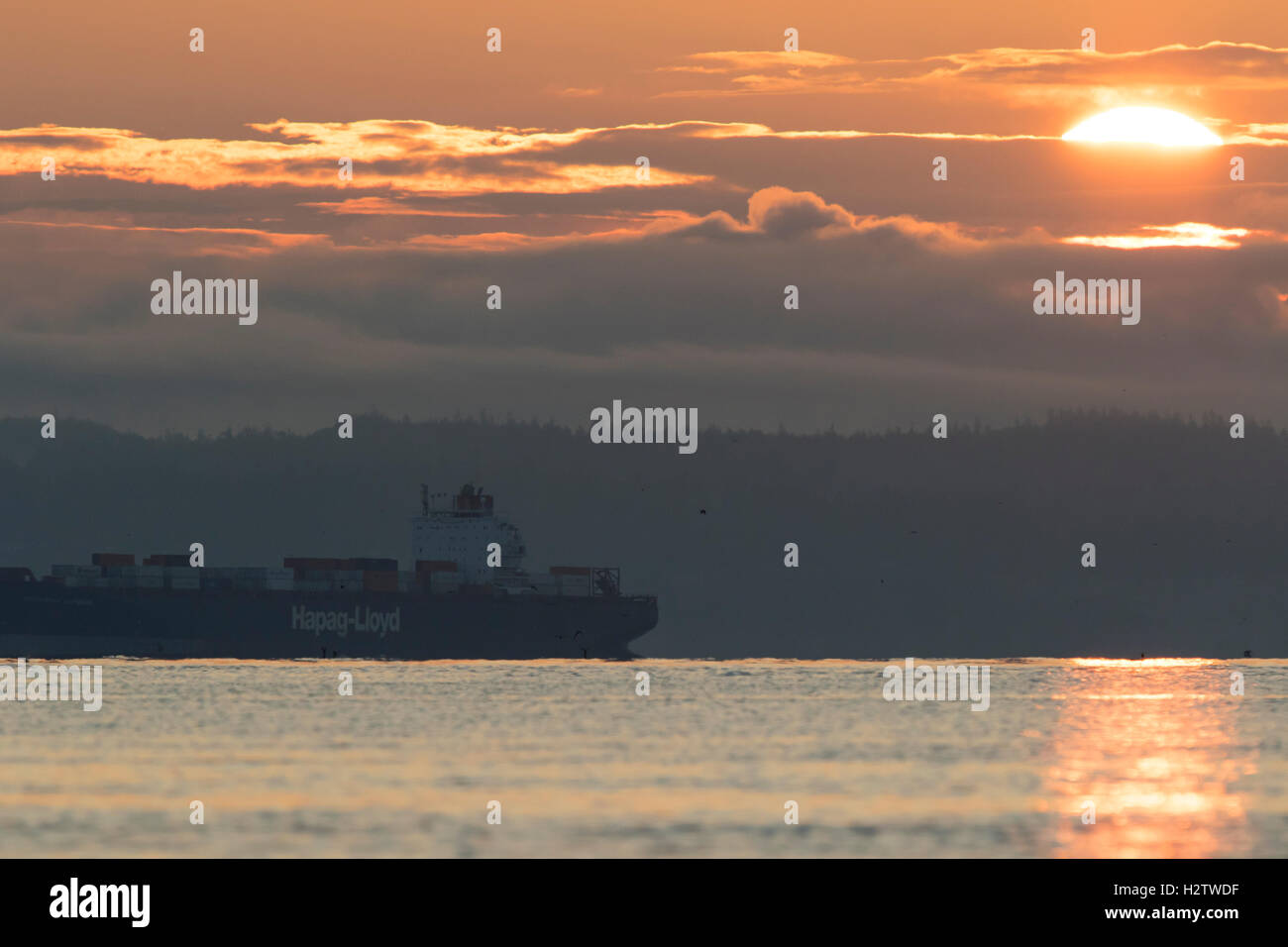 Puget Sound at sunrise with container ship. - Stock Image