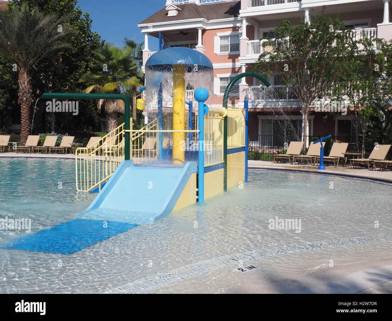 slide and climbing equipment in a kids pool.  The pool is in-ground and surrounded by empty lounge chairs. - Stock Image