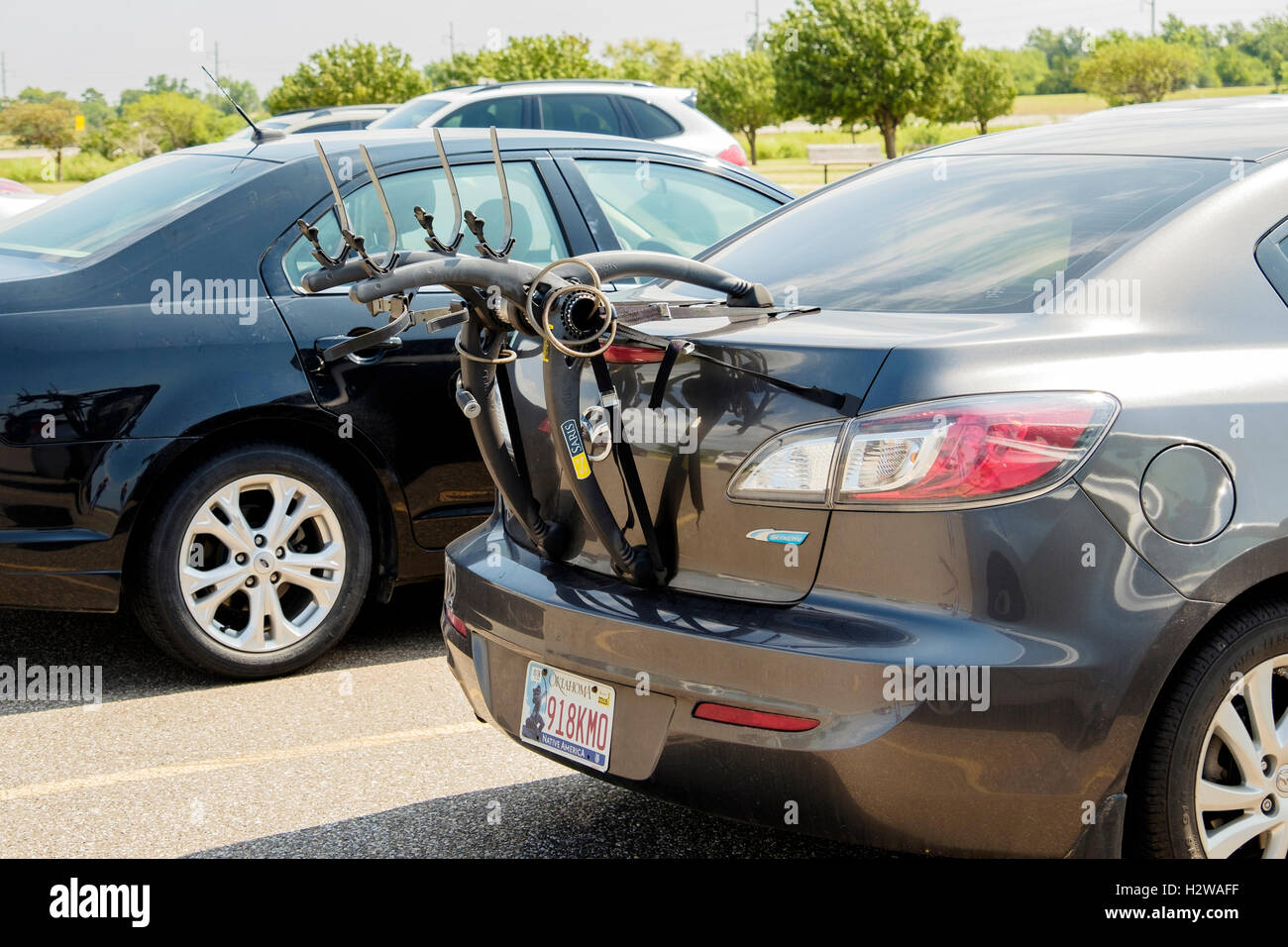 A Saris bicycle rack attached to the back of a car in a parking lot. Oklahoma City, Oklahoma, USA. - Stock Image