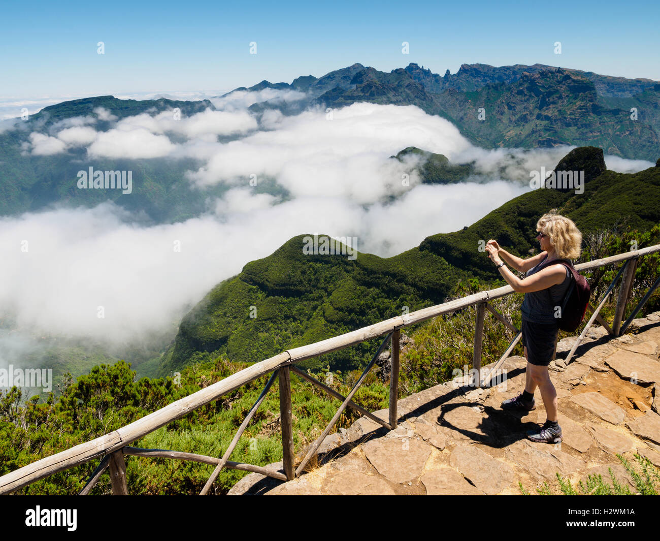 Madeira: A tourist takes a snapshot with her mobile phone from the Bica da Cana mountain, direction Sao Vicente - Stock Image