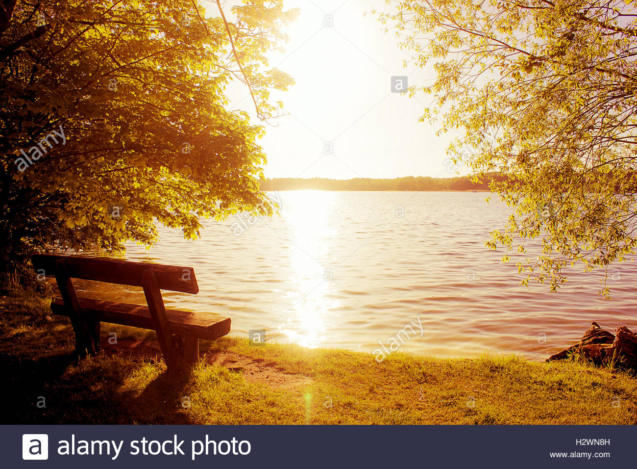 wooden park bench with view under golden morning sunlight tranquil stock photo 122267393 alamy. Black Bedroom Furniture Sets. Home Design Ideas