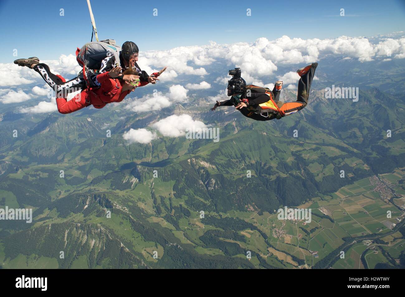 Camera flyer with a tandem pair in freefall - Stock Image