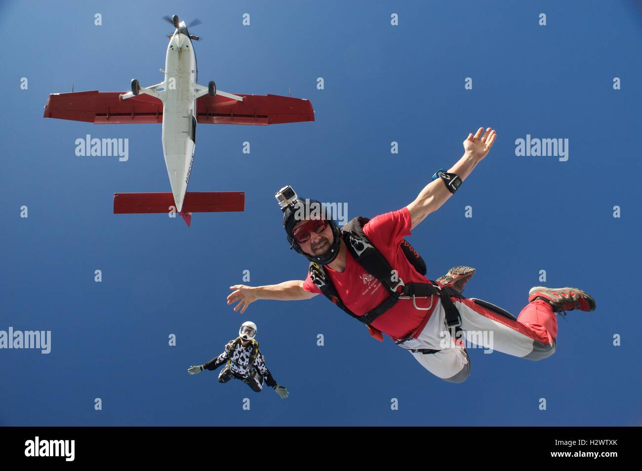 Two skydivers jumping off an airplane - Stock Image