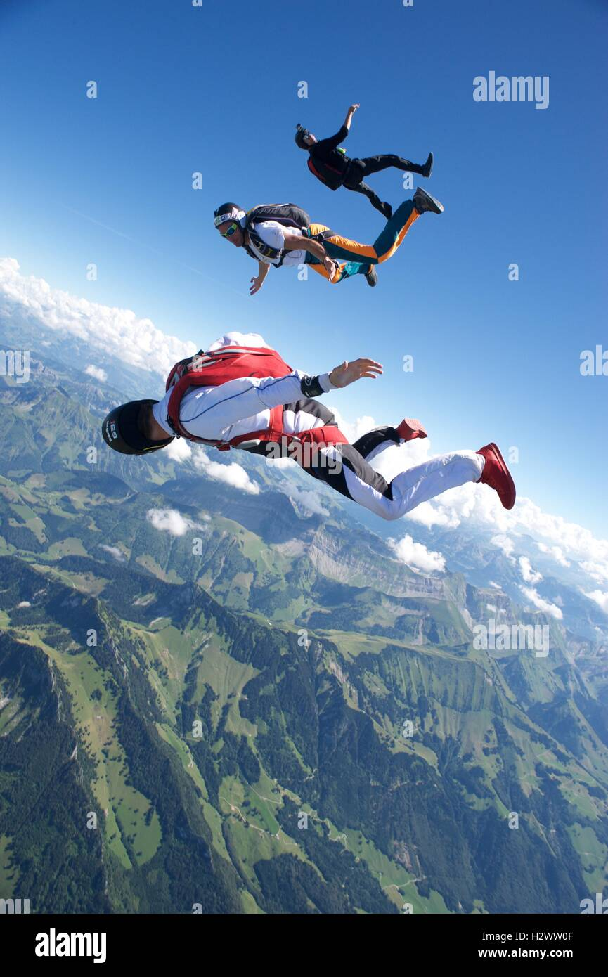Three skydivers tracking above Gruyeres in Switzerland - Stock Image
