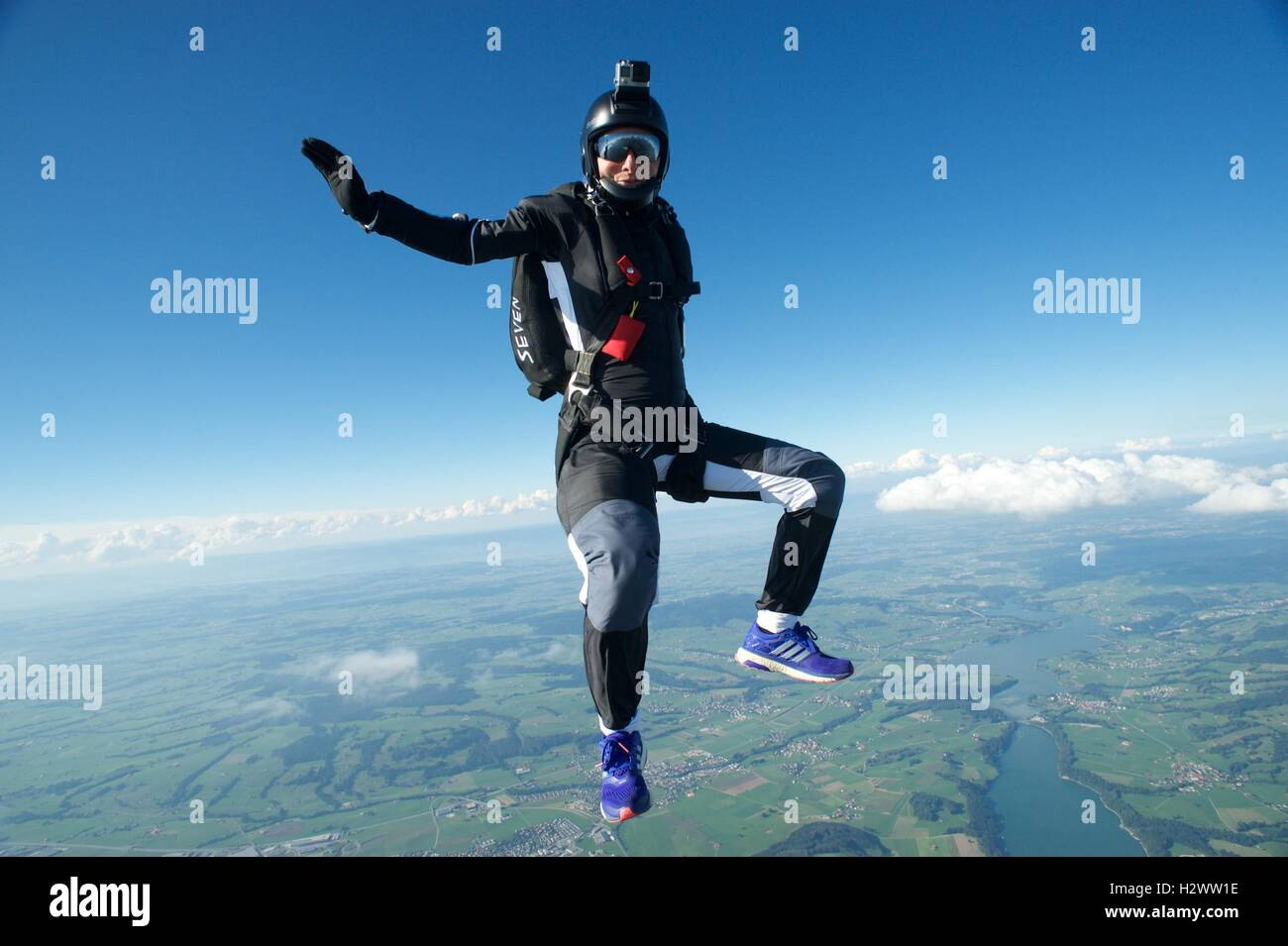 A woman sitting freefall position above Gruyeres - Stock Image