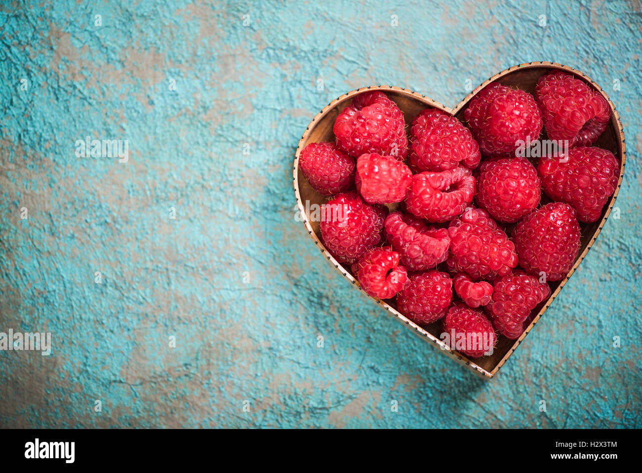 Raspberries in heart shape symbol, love for fruits and healthy living concept - Stock Image