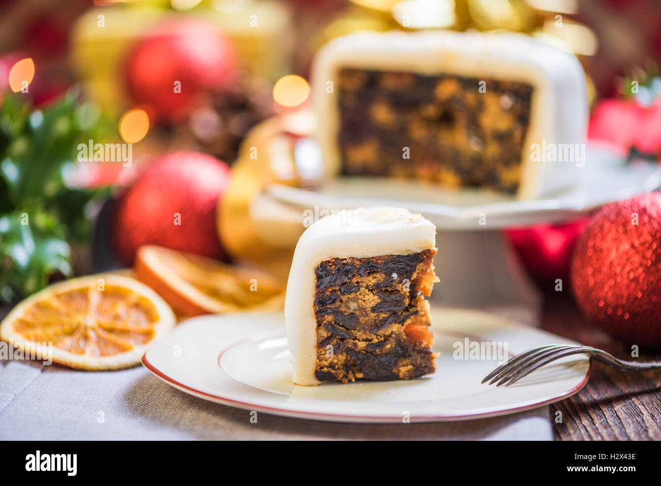 Slicing Christmas traditional festive fruit cake, Christmas ornaments and decorations Stock Photo
