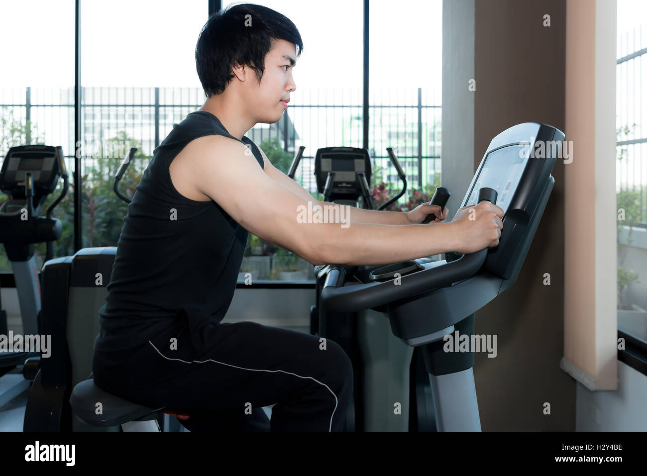 Man in the gym. Asian young man exercising his legs doing cardio training on bicycle in gym. - Stock Image