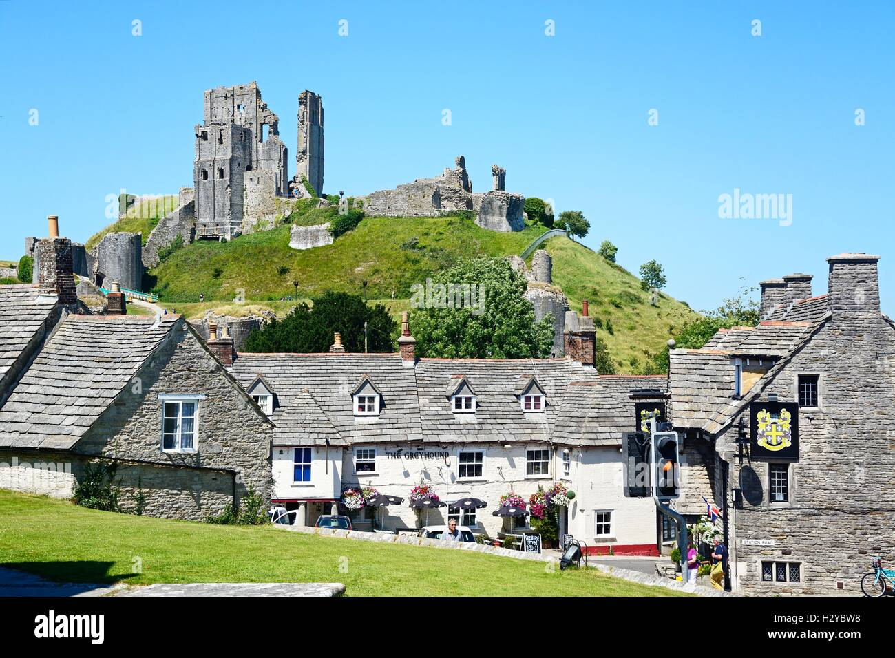 View of Corfe castle seen above The Greyhound Pub, Corfe, Dorset, England, UK, Western Europe. - Stock Image