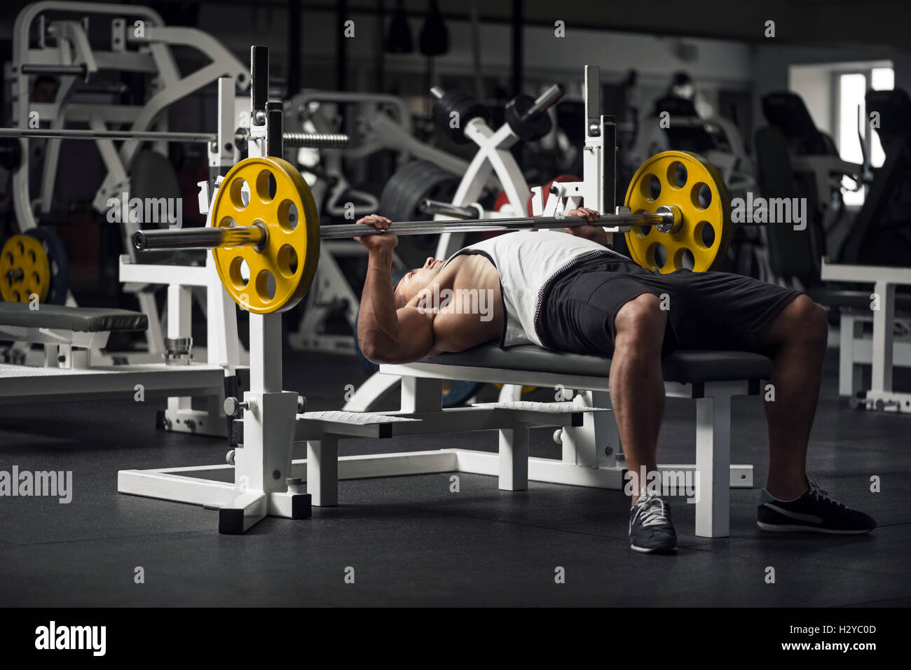 Strong athletic man preparing to lift a barbell - Stock Image