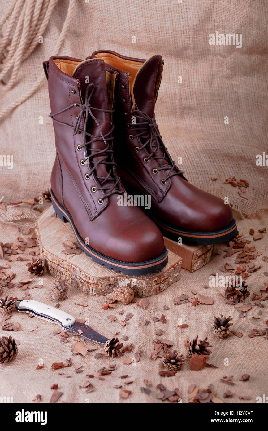 Brown boots on wooden background near pine cone, sackcloth - Stock Image
