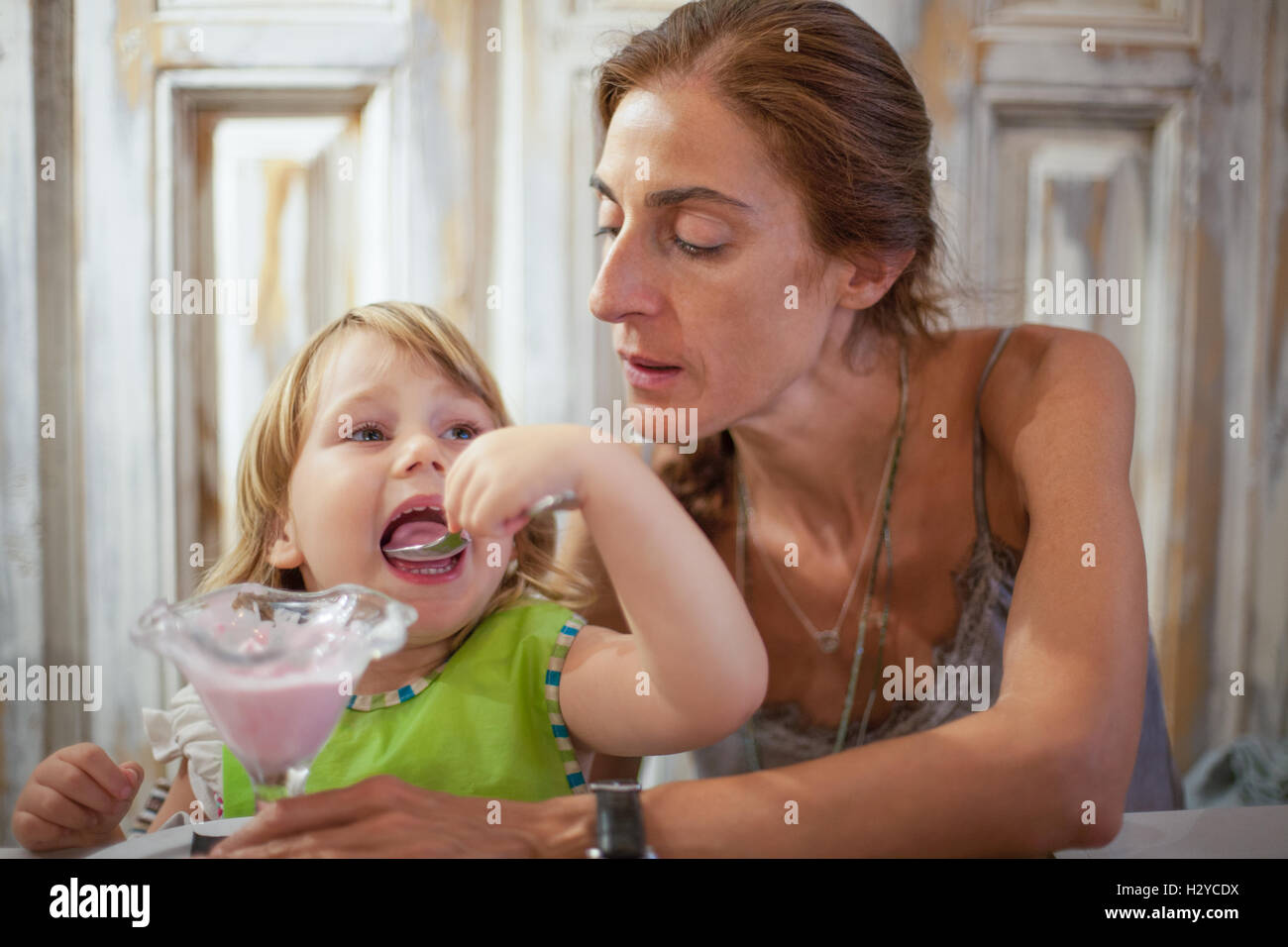 three years old child with green bib open big mouth eating strawberry ice cream with spoon from crystal cup next - Stock Image