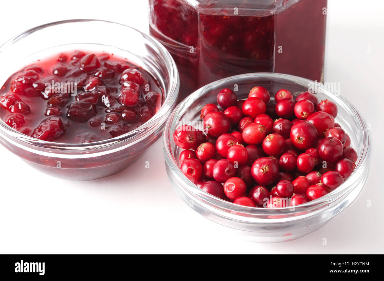 Lingonberries and lingonberry jam in glass bowls over white. Fresh red fruits of Vaccinium vitis-idaea, also mountain - Stock Image