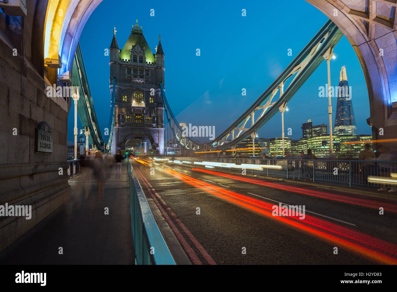 Skyline of Southwark with the Shard and gleam of traffic on the Tower Bridge over the river Thames at dusk, London, Stock Photo