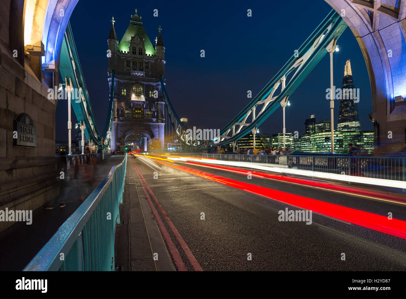 Skyline of Southwark with the Shard and gleam of traffic on the Tower Bridge over the river Thames at night, London, - Stock Image