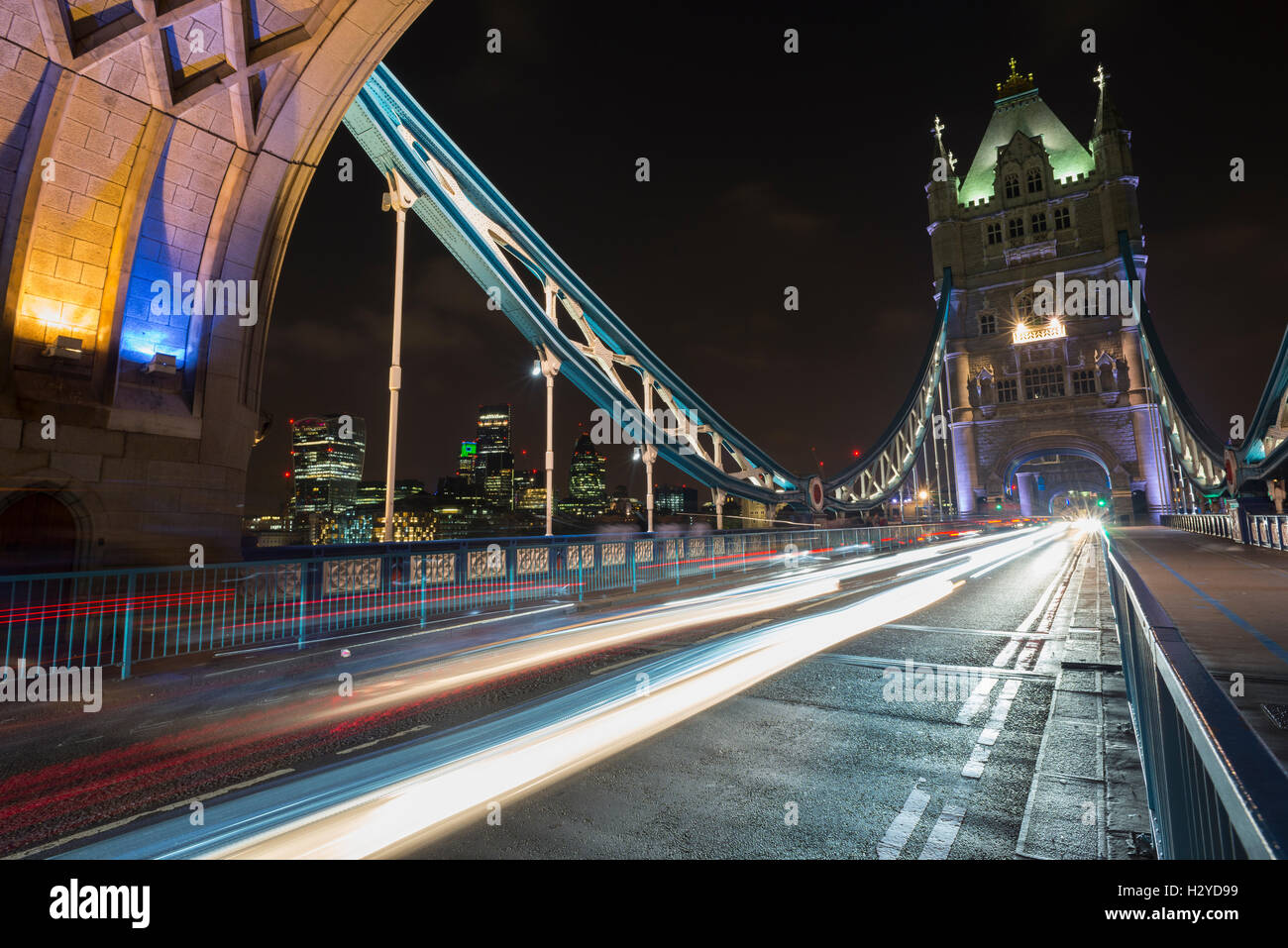 Skyline of the City of London behind the gleam of traffic on the Tower Bridge deck over the river Thames at night, - Stock Image