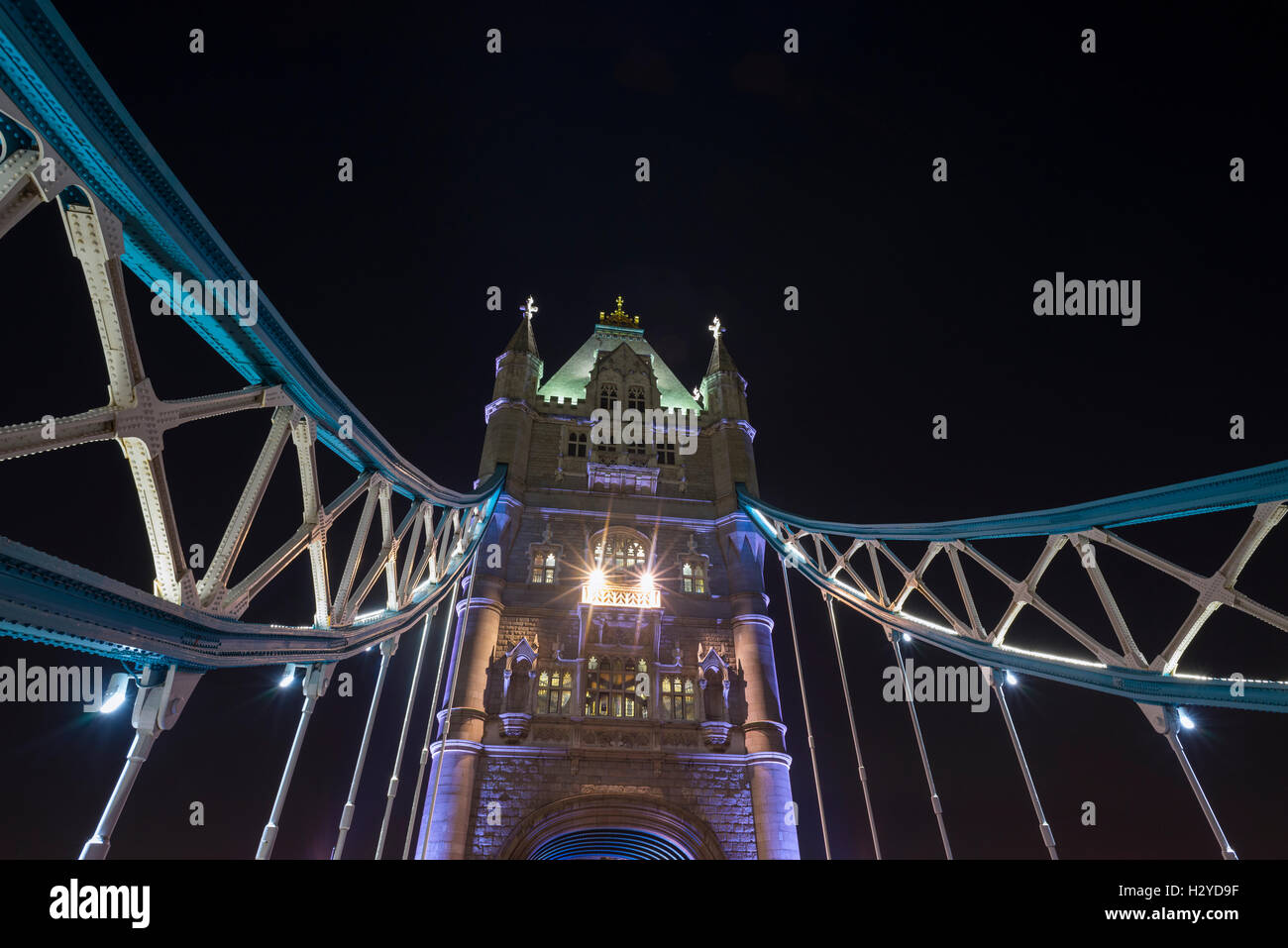 Looking up between illuminated steel chain elements to one tower of the Tower Bridge over the River Thames against Stock Photo