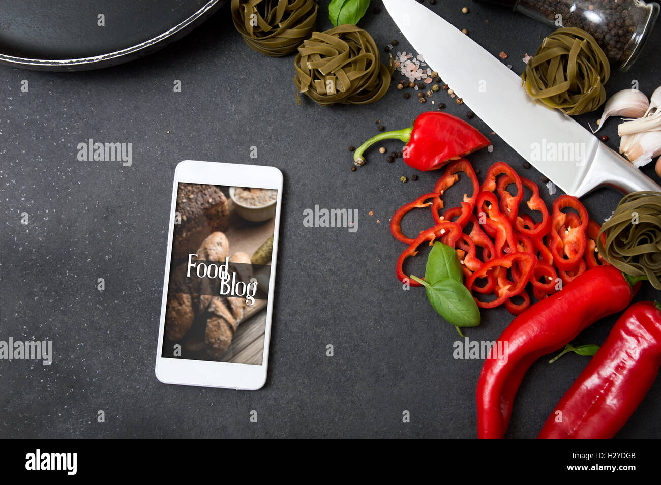 Smartphone with Food Blog application lying on stone countertop and surrounded by fresh herbs and hot spices Stock Photo