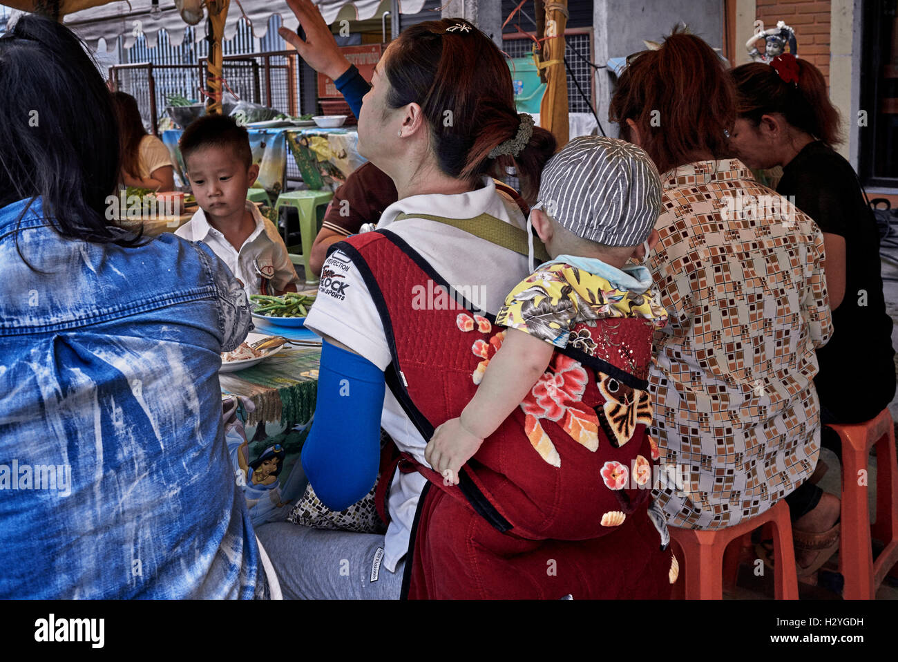 Thai mother and baby carried in a back sling harness and eating at an open air restaurant. Thailand S. E. Asia - Stock Image