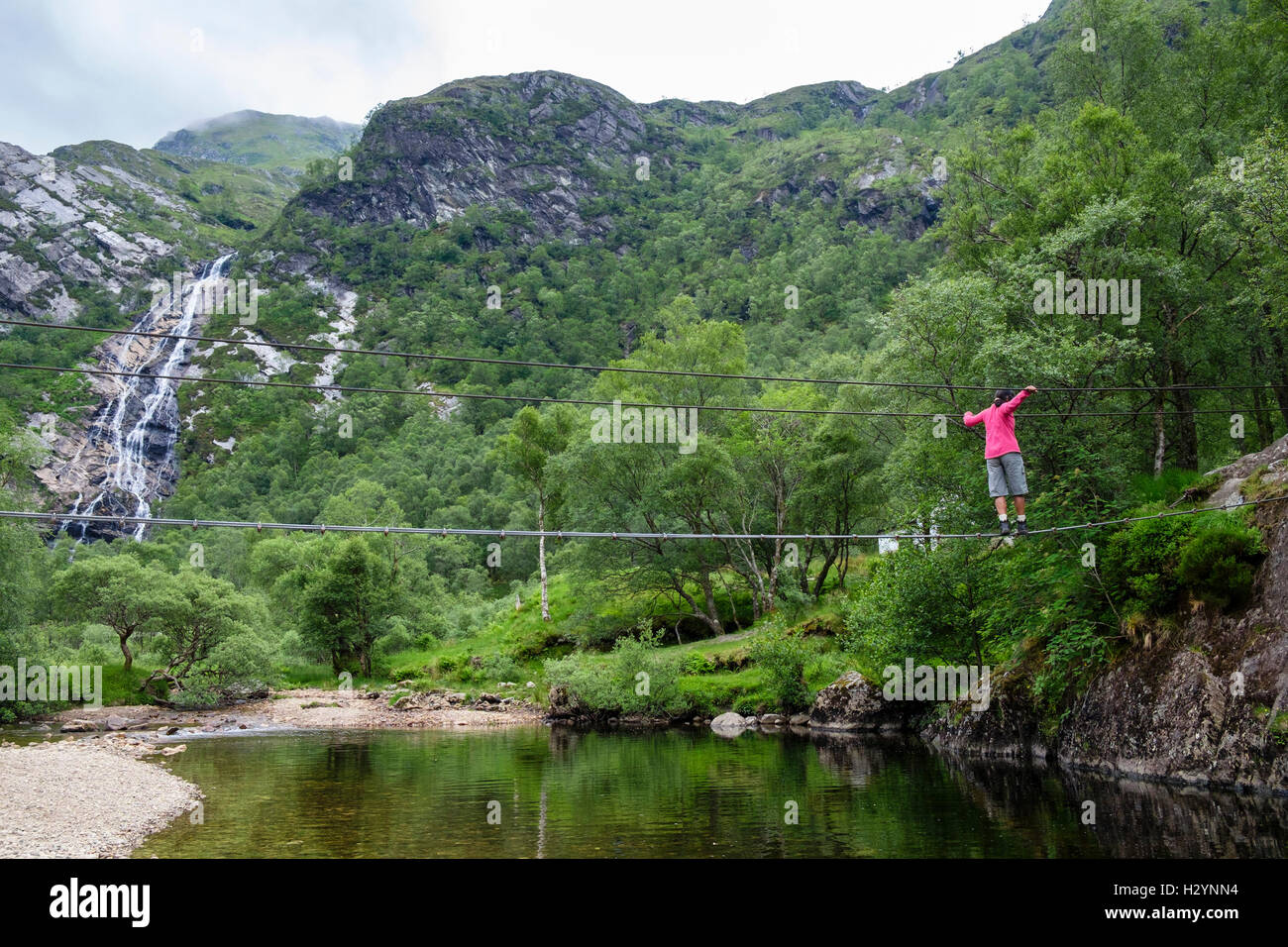 woman walking across steall wire bridge over water of nevis river