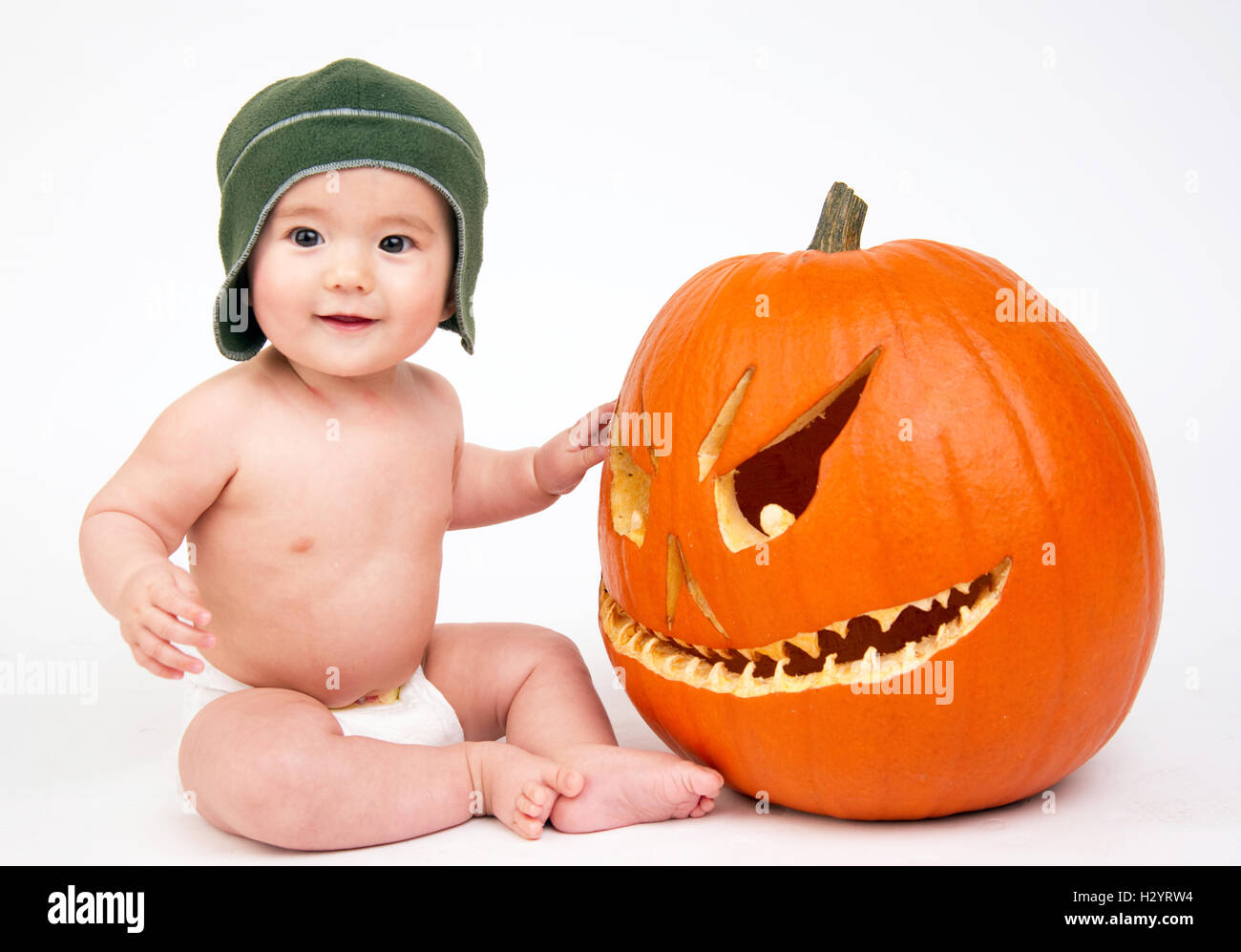 happy six month old boy sitting in diaper with carved halloween