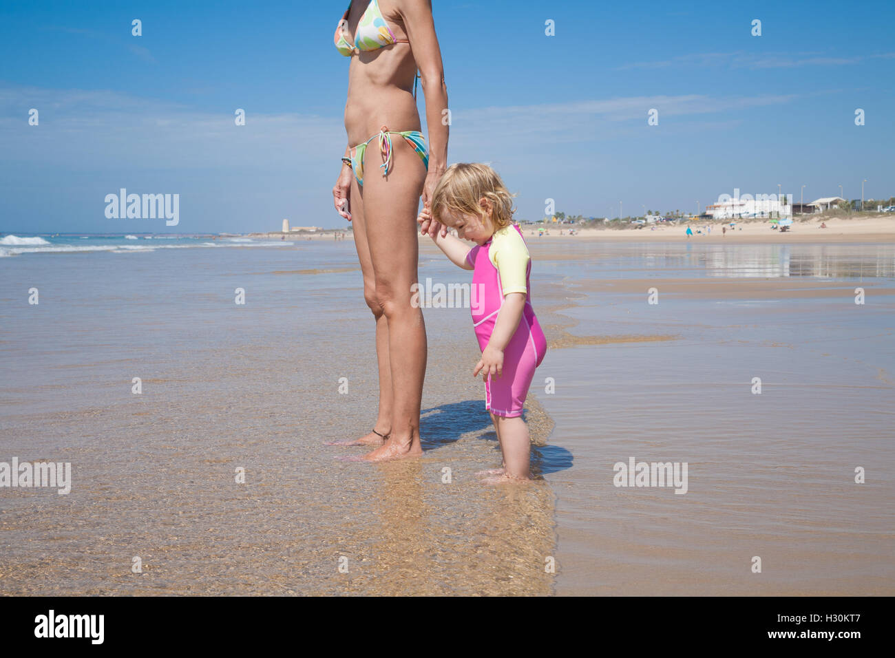 summer family of two years old blonde baby with pink and yellow swimsuit  holding hand with brunette woman mother in bikini stand