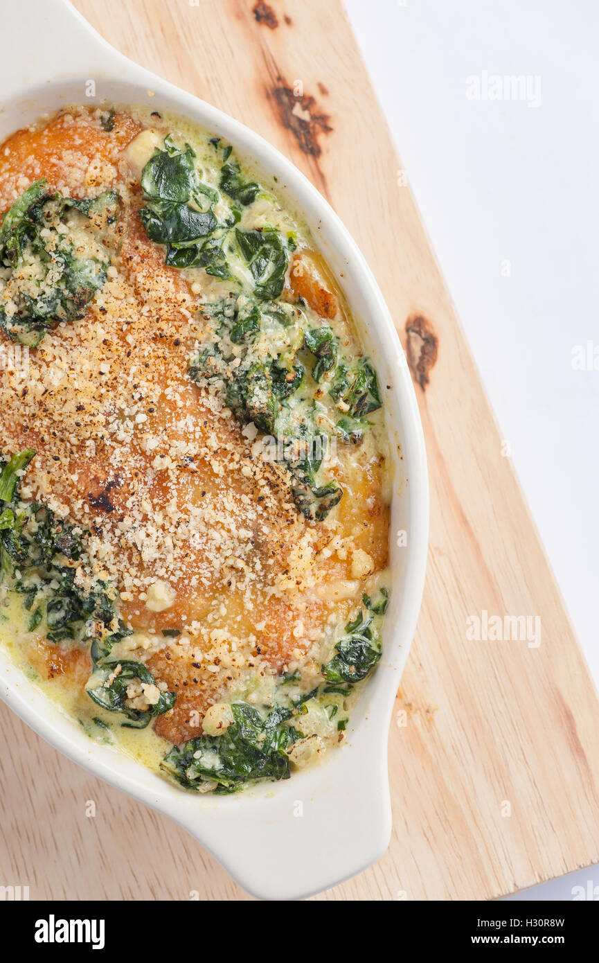 Modern style Spinach gratin (baked spinach with chesse) in ceramic bowl on wood plate - Stock Image