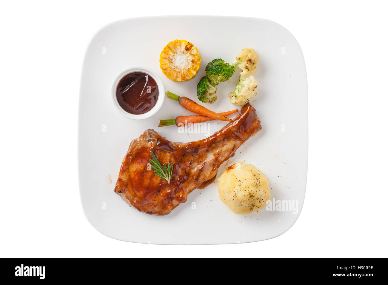 Top view of modern style pork chop with barbecue sauce, mashed potatoes, grilled vegetables in ceramic dish isolated - Stock Image