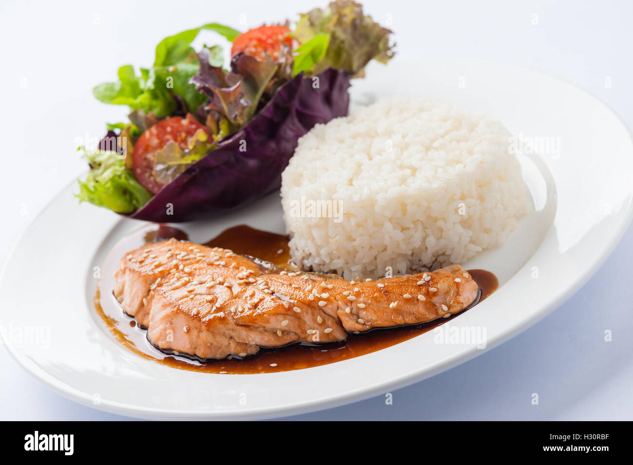 Fusion food style grilled salmon dressed with Japanese sweet sauce (Teriyaki) including Thai rice garnished with Stock Photo