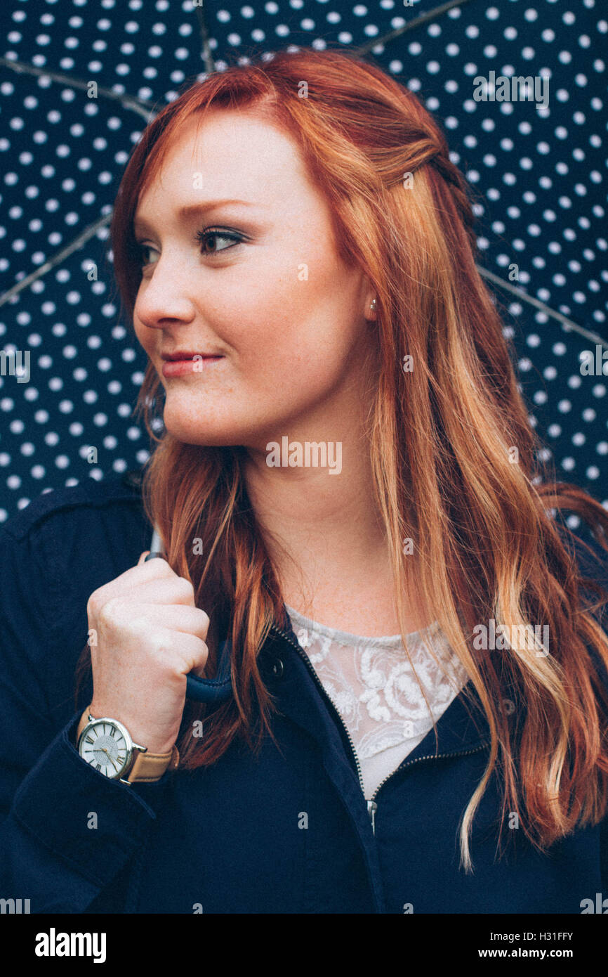 Stylized editorial shoot of a redhead girl with a polka dot umbrella, white shirt, blue coat, and watch. - Stock Image