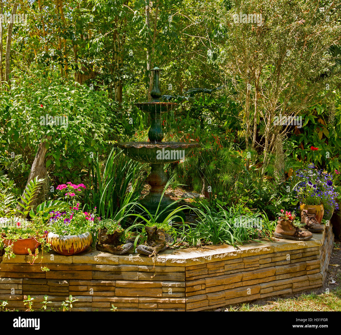 Garden with ornate fountain surrounded by emerald foliage, trees ...