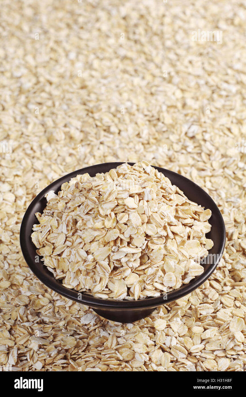 Black bowl of oatmeal and oat flakes as background - Stock Image