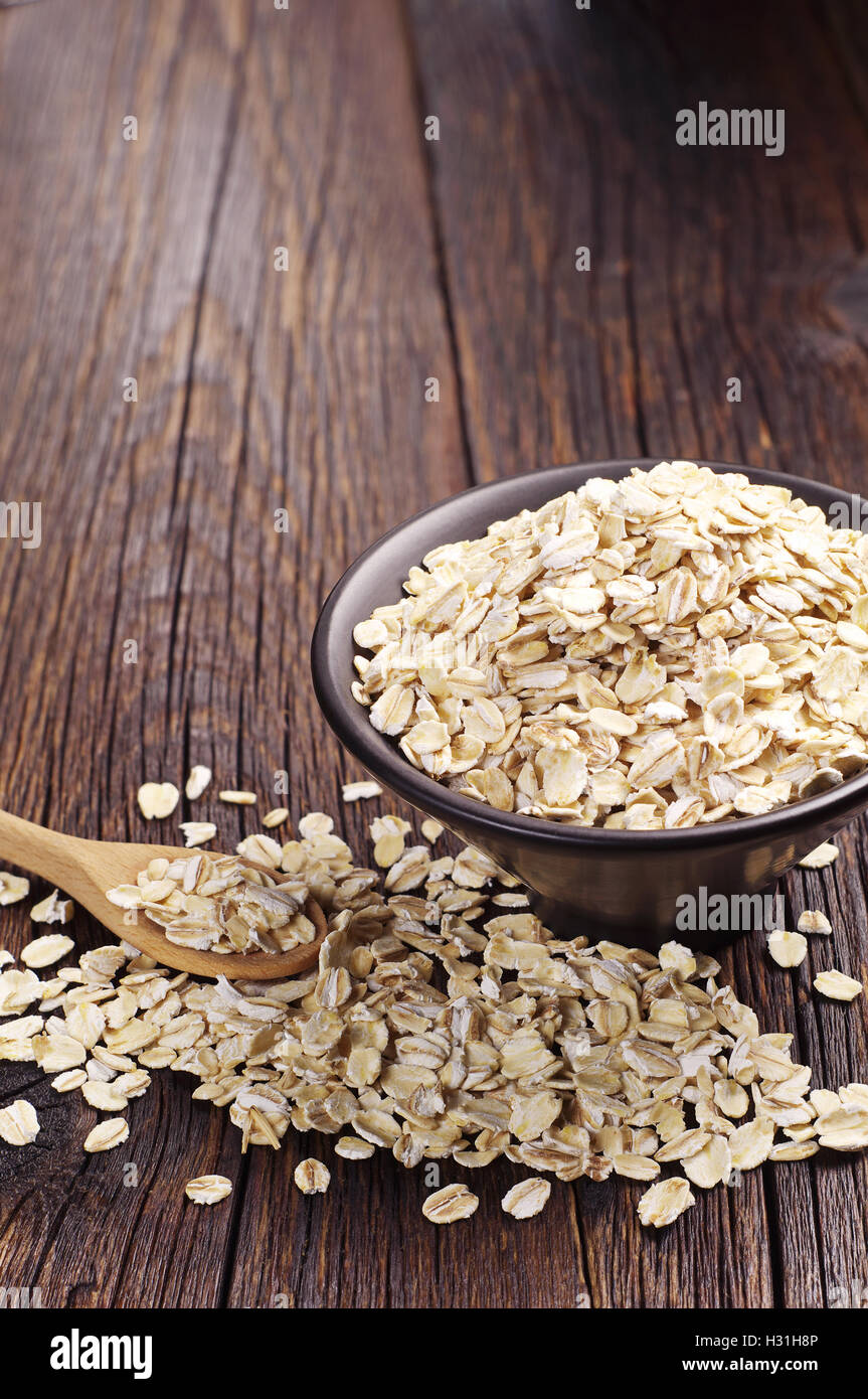 Oatmeal in black bowl and near on dark wooden table - Stock Image