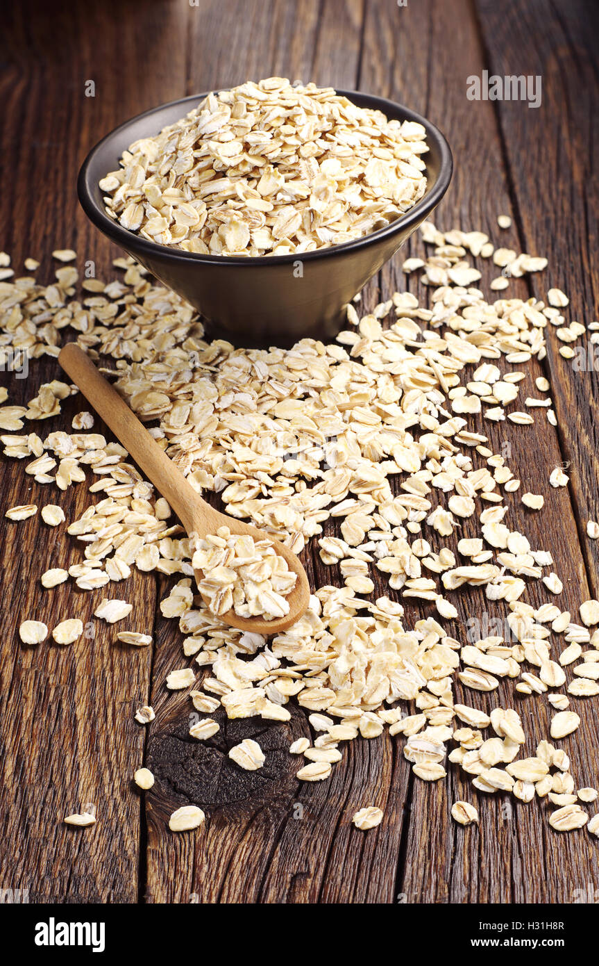 Uncooked oatmeal spilling from black bowl on a wooden background - Stock Image