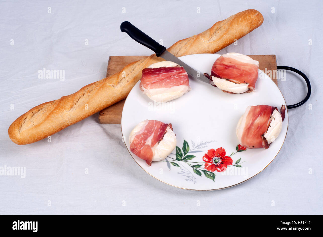 Fresh chese and baguette on display on a cutting board - Stock Image