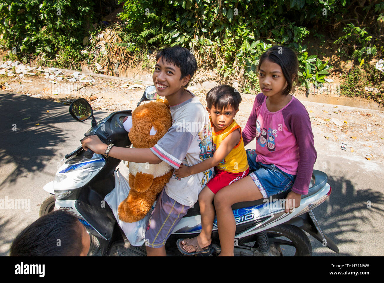 Indonesia, Bali, Lovina, Anturan Village three young children riding on motorbike - Stock Image